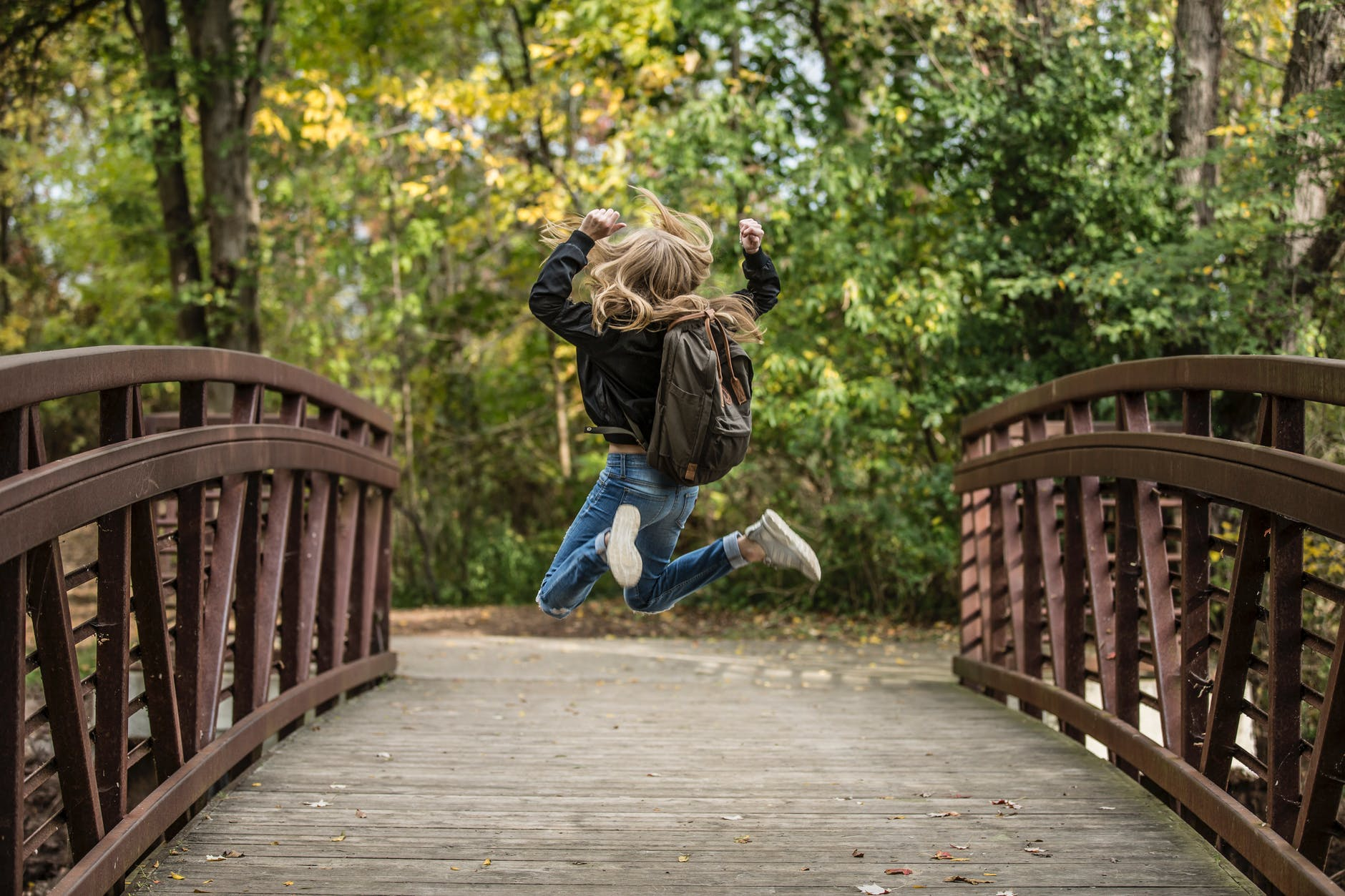 girl jumping on the bridge wearing black jacket